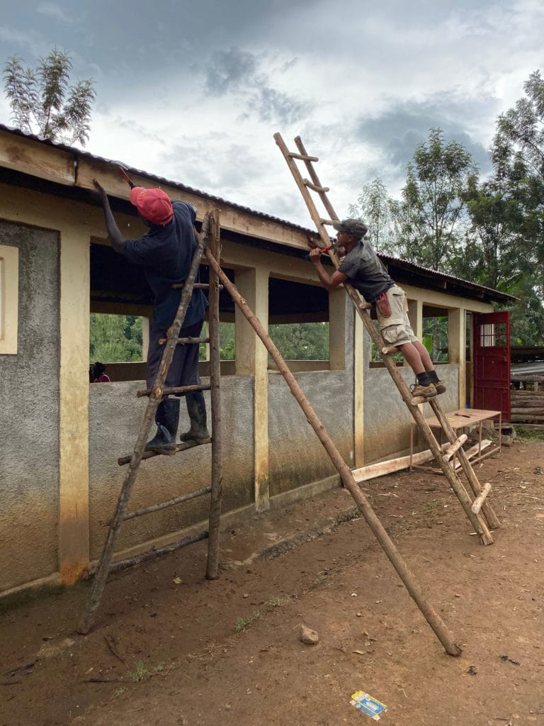 Brandon and Josephat installing the eaves trough for the new rainwater catchment tank for the kitchen and kids dining hall