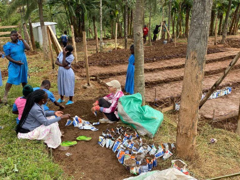 Marielle and the children Packing recycled milk bags with soil for planting tree seeds in the tree nursery